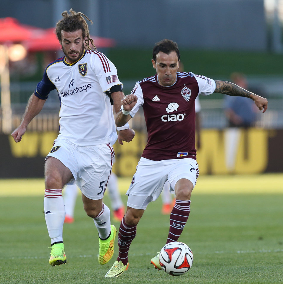 Photo - Real Salt Lake midfielder Kyle Beckerman, left, and Colorado Rapids forward Vicente Sanchez compete for the ball in the first half of an MLS soccer game in Commerce City, Colo., on Saturday, Aug. 2, 2014. (AP Photo/David Zalubowski)