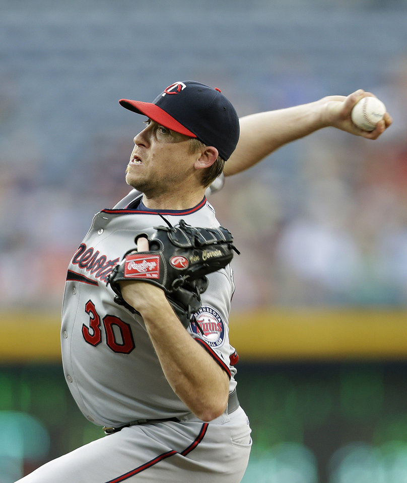 Photo - Minnesota Twins starting pitcher Kevin Correia (30) throws in the first inning of a baseball game against the Atlanta Braves Monday, May 20, 2013, in Atlanta. (AP Photo/John Bazemore)