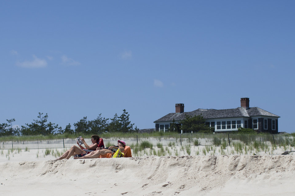 Photo - In this photo taken on Friday, July 11, 2014, beachgoers relax near a beachfront property in Southampton, N.Y. Studies show the gap separating the rich from the working poor has been ever-widening in recent years and few places provide that evidence as starkly as Long Island's Hamptons. (AP Photo/John Minchillo)