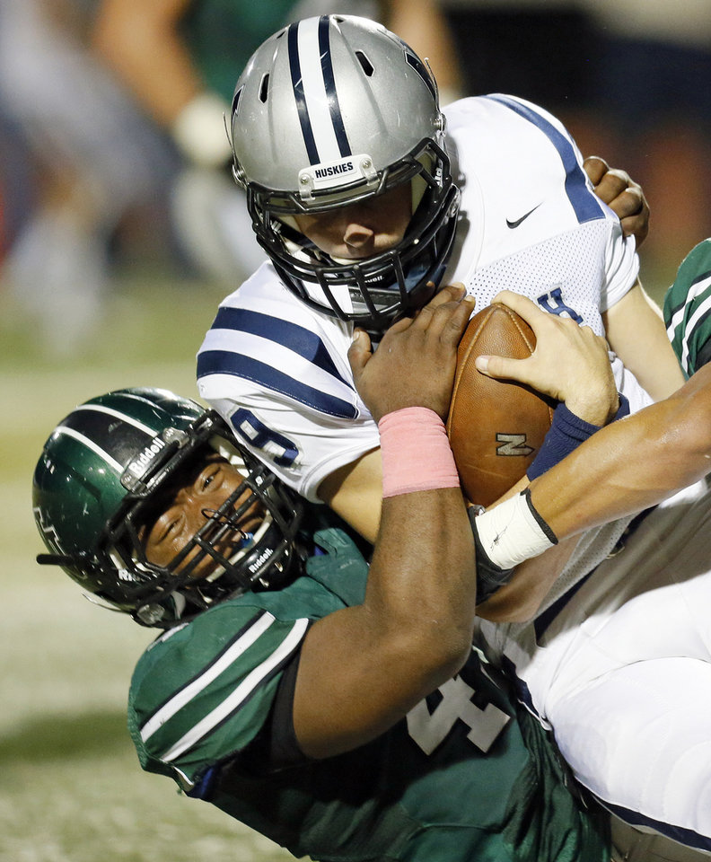 Photo - Norman North's Justin Martin (45) brings down Edmond North quarterback Luke Hoskins (9) on a keeper during a high school football game between Edmond North and Norman North in Norman, Okla., Thursday, Oct. 11, 2012. Photo by Nate Billings, The Oklahoman