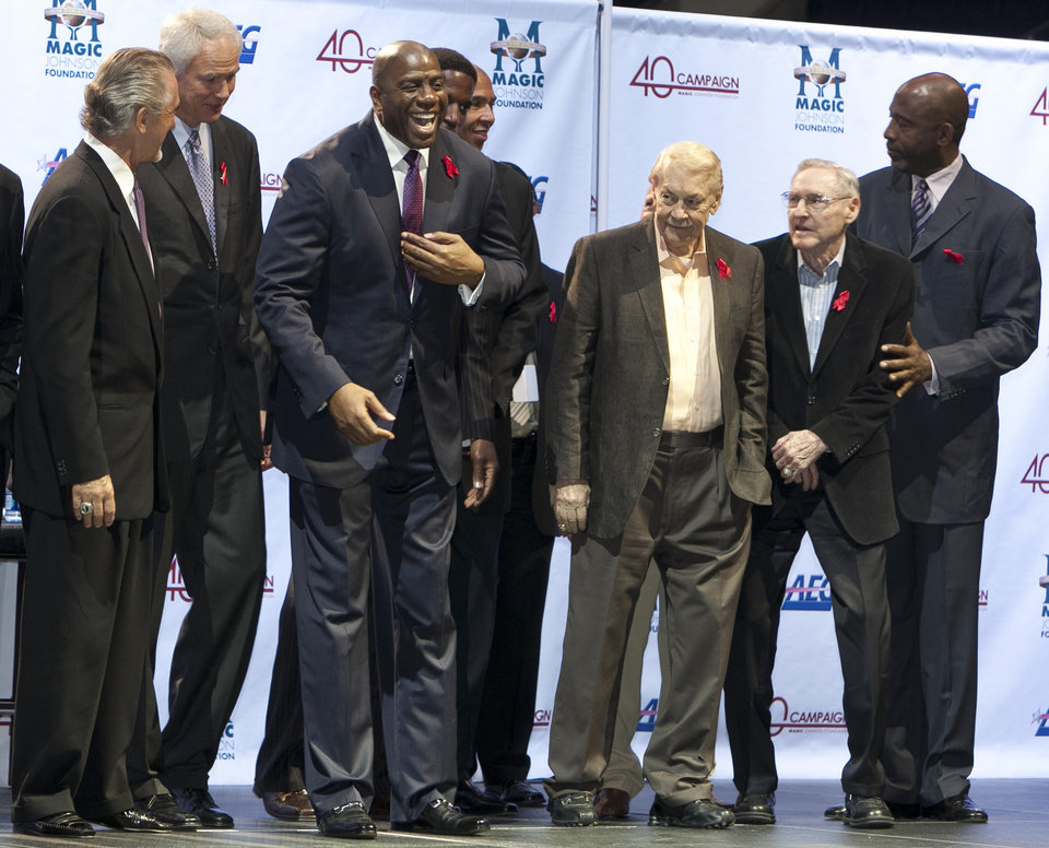 FILE - In this Nov. 7, 2011 file photo, Los Angeles Lakers owner Jerry Buss, third from right, looks towards Magic Johnson, third from left, during a ceremony of the Magic Johnson Foundation in Los Angeles. Also shown are former Lakers team members Pat Riley, left, Mitch Kupchak, second from left, Bill Sharman, second from right, and James Worthy, right. Buss, the Lakers\' playboy owner who shepherded the NBA franchise to 10 championships, has died. He was 79. Bob Steiner, an assistant to Buss, confirmed Monday, Feb. 18, 2013 that Buss had died in Los Angeles. Further details were not available.(AP Photo/Damian Dovarganes, FIle)