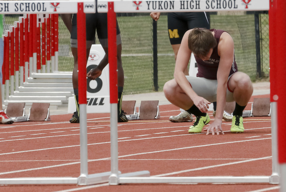 Photo - Edmond Memorial's Jesse Cossey kneels down to get focused before his race in the 6A boys 110m hurdles during the class 5A and 6A track state championships at Yukon High School on on Friday, May 10, 2013, in Yukon, Okla.Photo by Chris Landsberger, The Oklahoman
