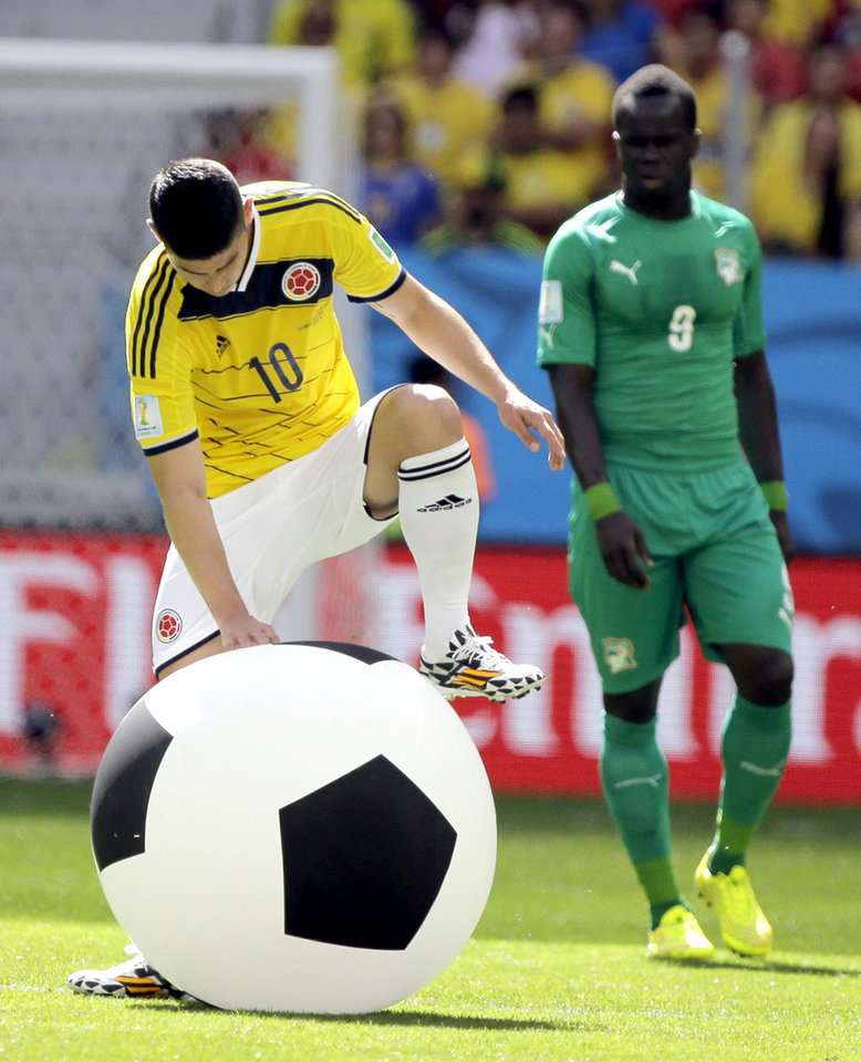 Photo - Colombia's James Rodriguez deflates a large inflatable ball that was thrown onto the pitch during the group C World Cup soccer match between Colombia and Ivory Coast at the Estadio Nacional in Brasilia, Brazil, Thursday, June 19, 2014.  (AP Photo/Marcio Jose Sanchez)