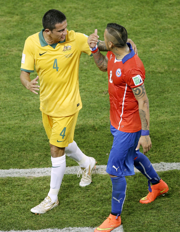 Photo - Australia's Tim Cahill, left, talks with Chile's Arturo Vidal as they leave the pitch after the first half during the group B World Cup soccer match between Chile and Australia in the Arena Pantanal in Cuiaba, Brazil, Friday, June 13, 2014. (AP Photo/Michael Sohn)