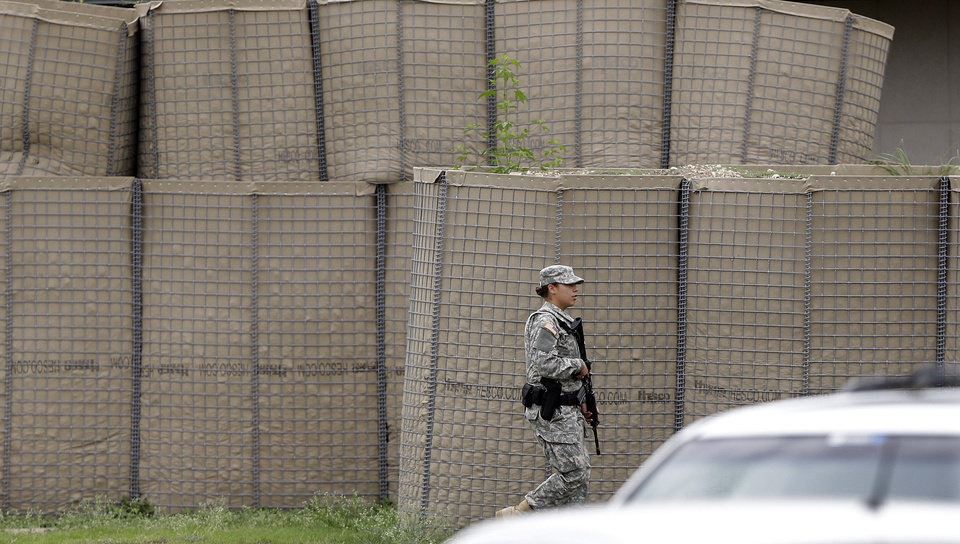 Photo - An armed guard walks around the fortified Lawrence William Judicial Center as the sentencing phase for Maj. Nidal Hasan continues, Tuesday, Aug. 27, 2013, in Fort Hood, Texas. Hasan was convicted of killing 13 of his unarmed comrades in the deadliest attack ever on a U.S. military base. (AP Photo/Eric Gay)