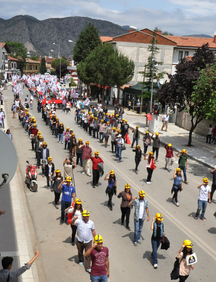 Photo - Several hundred members of the Union of Turkish Youth wear miner's helmets during a march to commemorate the Soma coal mine victims, in Amasya, Turkey, Sunday, May 18, 2014. Eighteen people, including mining company executives, have been detained as Turkish officials investigate the mining disaster that killed 301 people, a domestic news agency reported Sunday. (AP Photo/Emre Tazegul)