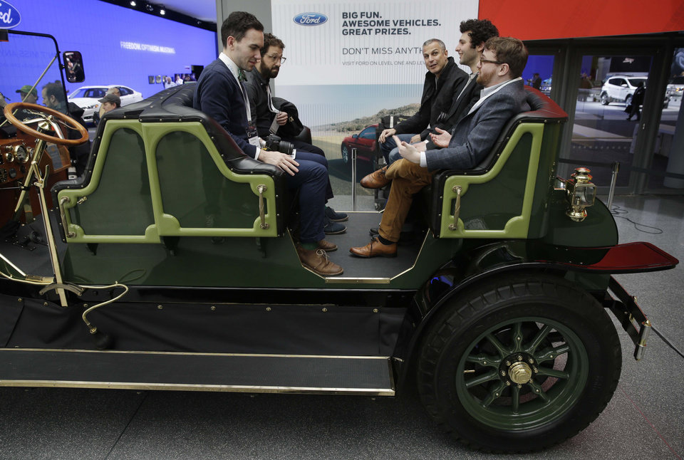 Visitors to the New York International Auto Show sit in an electric carriage prototype in New York, Thursday, April 17, 2014.  A prototype of the old-timey electric cars that Mayor Bill de Blasio would like to take the place of horse-drawn carriages on New York City streets will be unveiled at the New York Auto Show on Thursday. (AP Photo/Seth Wenig)