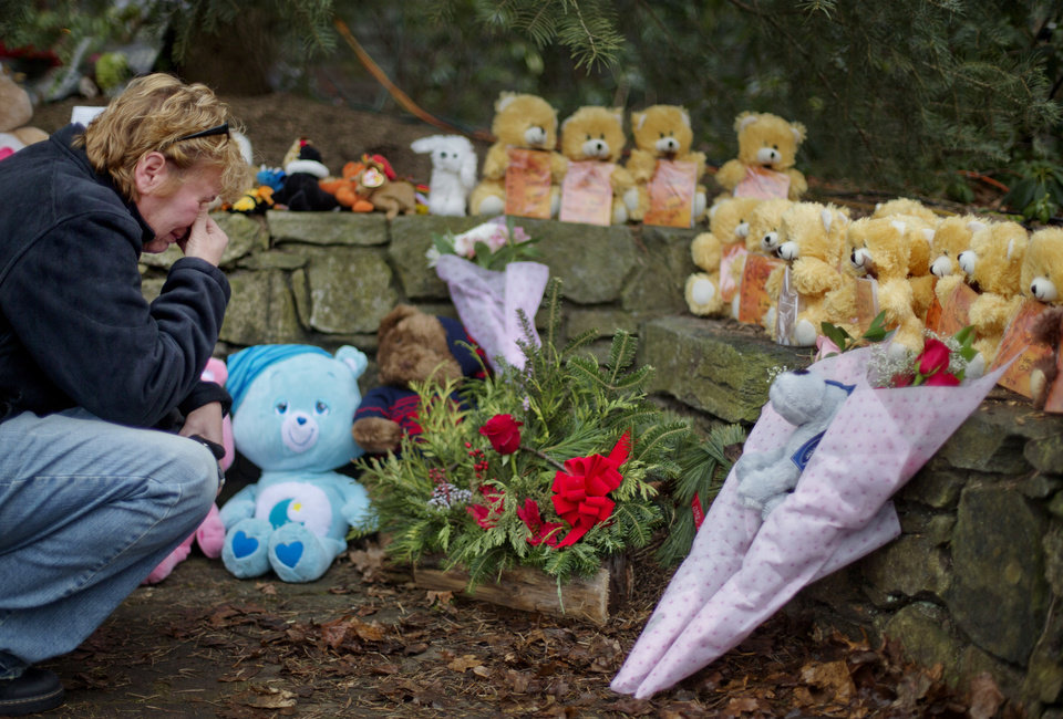 Cheryl Girardi, of Middletown, Conn., kneels beside 26 teddy bears, each representing a victim of the Sandy Hook Elementary School shooting, at a sidewalk memorial, Sunday, Dec. 16, 2012, in Newtown, Conn. A gunman walked into Sandy Hook Elementary School in Newtown Friday and opened fire, killing 26 people, including 20 children.(AP Photo/David Goldman) ORG XMIT: CTDG114