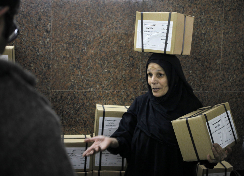 Photo - An Egyptian worker carries boxes of ballots at the Giza courthouse, in Cairo, Egypt, Monday, Jan. 13, 2014. The January 14-15 vote on the draft constitution will be the first real test of the post-Morsi regime. A comfortable