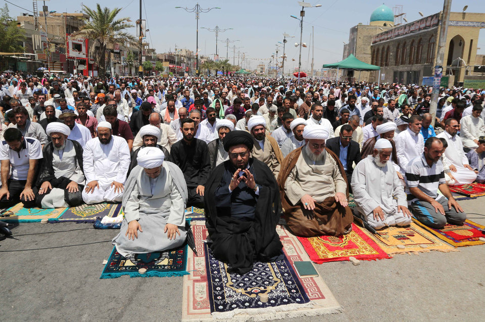 Photo - Followers of Shiite cleric Muqtada al-Sadr attend open-air Friday prayers in the Shiite stronghold of Sadr City, Baghdad, Iraq, Friday, July 11, 2014. The lightning sweep by the militants over much of northern and western Iraq the past month has dramatically hiked tensions between the country's Shiite majority and Sunni minority. At the same time, splits have grown between the Shiite-led government in Baghdad and the Kurdish autonomous region in the north. (AP Photo/Karim Kadim)