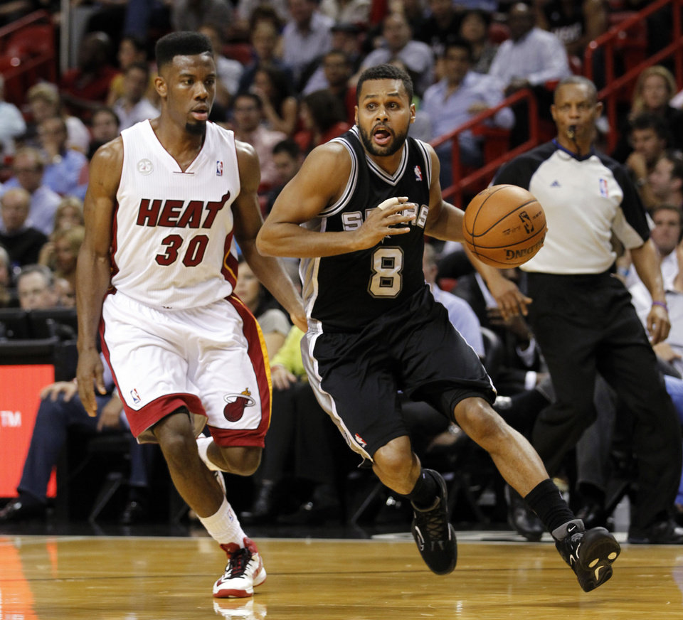 San Antonio Spurs' Patrick Mills (8) drives around Miami Heat's Norris Cole (30) in the first half of an NBA basketball game on Thursday, Nov. 29, 2012, in Miami. ( AP Photo/Alan Diaz)