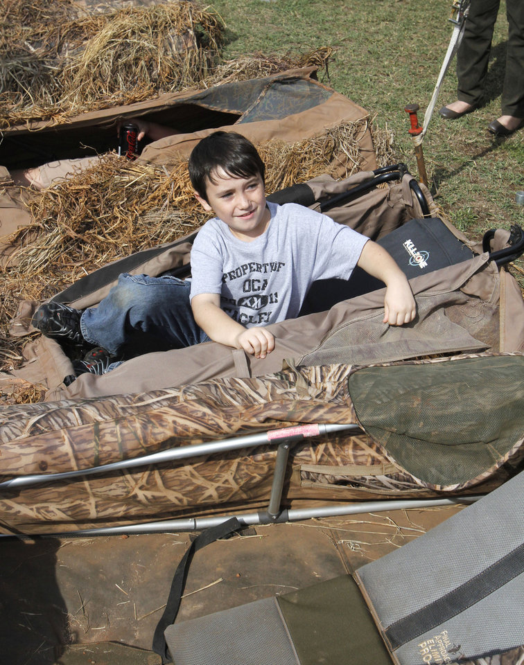 Photo - Eight year old Myles Campbell, from Oklahoma Christian Academy, opens up a duck blind during school day of the Oklahoma Wildlife Expo at the Lazy E Arena and Ranch in Guthrie, OK, Friday, September 28, 2012,  By Paul Hellstern, The Oklahoman