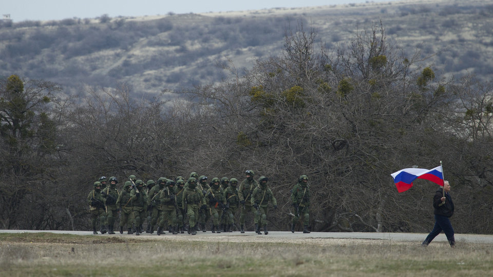 Photo - Russian solders walk as a local resident waves with Russian flag outside of a Ukrainian military base in the village of Perevalne, outside of Simferopol, Ukraine, on Sunday, March 2, 2014. Hundreds of armed men in trucks and armored vehicles surrounded the Ukrainian military base Sunday in Crimea, blocking its soldiers from leaving. (AP Photo/Ivan Sekretarev)