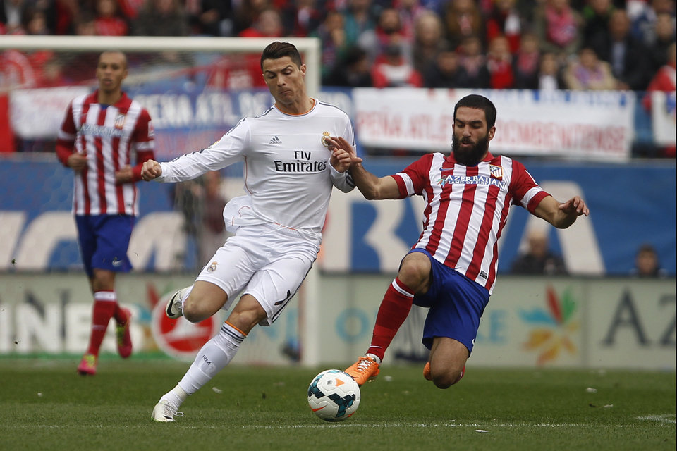 Photo - Real's Cristiano Ronaldo, left, in action with Atletico's Arda Turan, right , during a Spanish La Liga soccer match between Atletico de Madrid and Real Madrid at the Vicente Calderon stadium in Madrid, Spain, Sunday, March 2, 2014. (AP Photo/Gabriel Pecot)