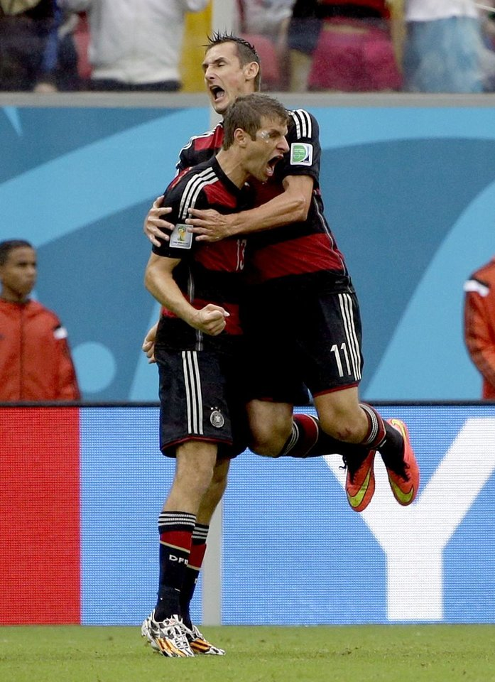Photo - Germany's Thomas Mueller celebrates with his teammate Miroslav Klose after scoring his side's first goal during the group G World Cup soccer match between the United States and Germany at the Arena Pernambuco in Recife, Brazil, Thursday, June 26, 2014.  (AP Photo/Ricardo Mazalan)