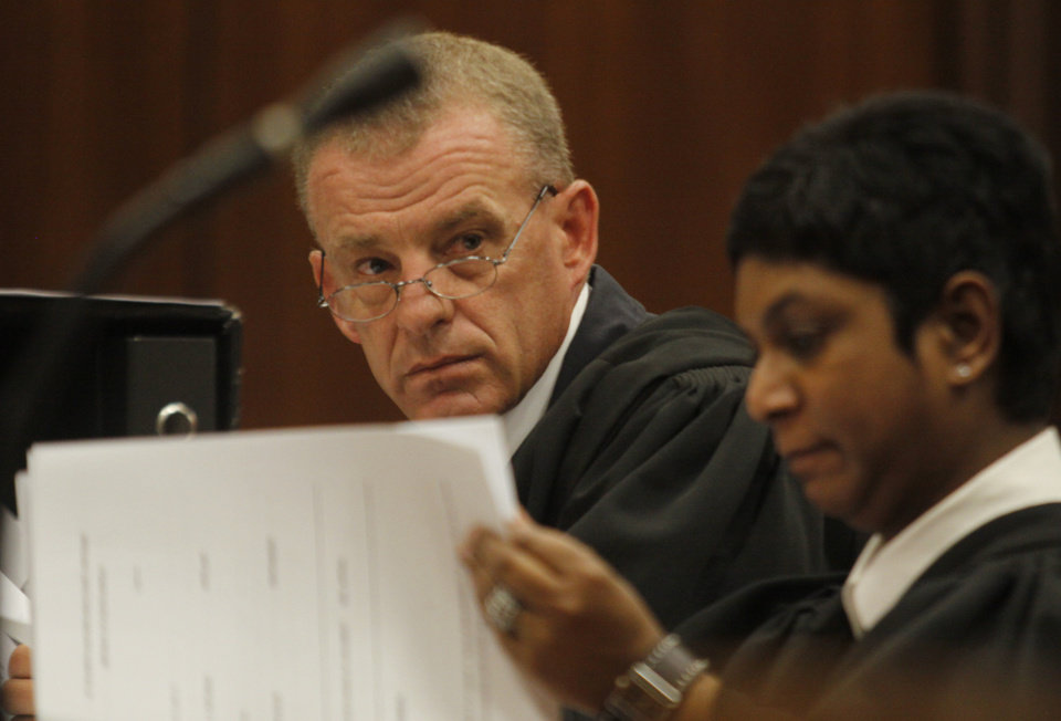 Photo - State prosecutor Gerrie Nel, prepares for a hearing in the Pretoria, South Africa high court, Thursday, March 28, 2013. The state is opposing the relaxation of bail conditions in the charges against athlete Pistorius who is charged with the shooting death of his girlfriend Reeva Steenkamp last month. (AP Photo/Denis Farrell)