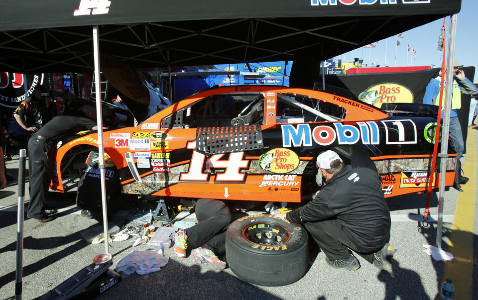 Photo - Crew members for driver Tony Stewart work on his car after he had engine problems during a practice for the NASCAR Daytona 500 auto race at Daytona International Speedway in Daytona Beach, Fla., Saturday, Feb. 15, 2014. (AP Photo/Terry Renna)
