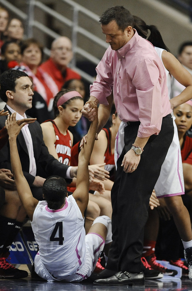 Photo - Louisville head coach Jeff Walz helps Connecticut's Moriah Jefferson up after Jefferson fell into the Louisville bench during the second half of an NCAA women's college basketball game, Sunday, Feb. 9, 2014, in Storrs, Conn. Connecticut won 81-64. (AP Photo/Jessica Hill)