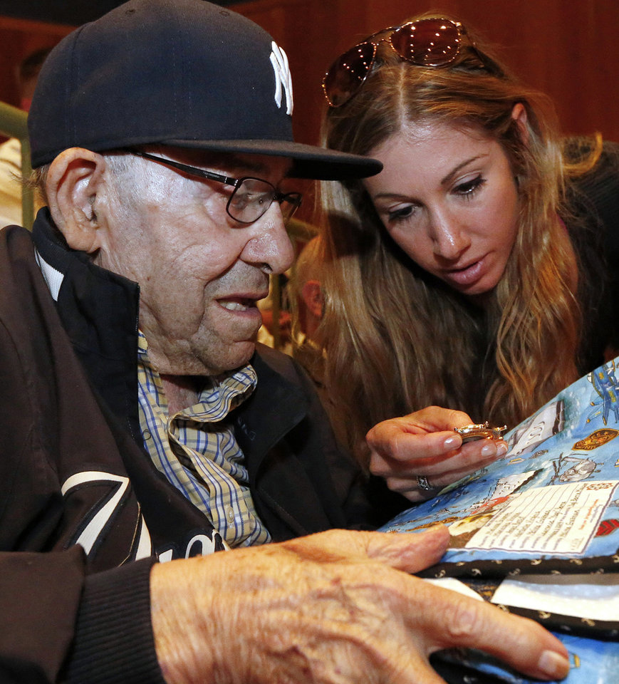 Photo - Baseball Hall of Famer Yogi Berra and his granddaughter Lindsay Berra look at a quilt and a medal that was presented to him by members of the U.S. Navy during a D-Day presentation at the Yogi Berra Museum in Montclair, N.J.,  Friday, June 6, 2014. Berra served in the navy 70 years ago as part of the D-Day invasion. (AP Photo/Rich Schultz)