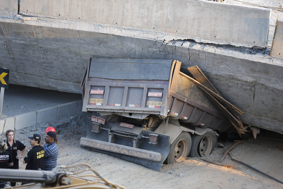 Photo - A truck is trapped underneath a collapsed bridge in Belo Horizonte, Brazil, Thursday, July 3, 2014. The overpass under construction collapsed Thursday in the Brazilian World Cup host city. The collapse took place on a main avenue, the expansion of which was part of the World Cup infrastructure plan but, like most urban mobility projects related to the Cup, was not finished on time for the event. (AP Photo/Victor R. Caivano)