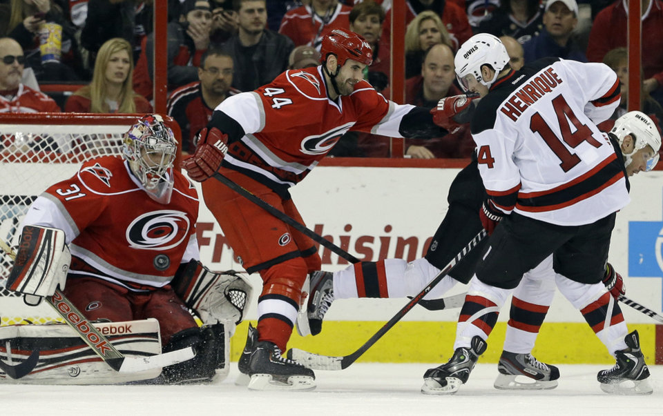 Photo - Carolina Hurricanes goalie Dan Ellis (31) and teammate Jay Harrison (44) defend against New Jersey Devils' Adam Henrique (14) during the second period of an NHL hockey game in Raleigh, N.C., Thursday, March 21, 2013. Henrique scored on the play. (AP Photo/Gerry Broome)