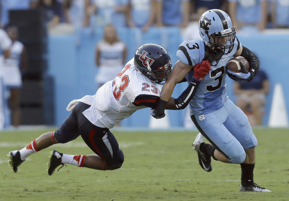 Photo - North Carolina's Ryan Switzer (3) runs the ball as Liberty's Justin Guillory (23) moves in to make the tackle during the first half of an NCAA college football game in Chapel Hill, N.C., Saturday, Aug. 30, 2014. (AP Photo/Gerry Broome)