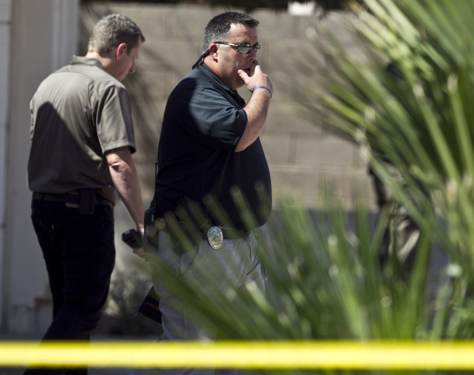 Photo -   An investigator walks in front of the house, where police say a man shot and killed four people, including a toddler, before killing himself, in Gilbert, Ariz., on Wednesday, May 2, 2012. Police say the man was armed with several firearms, and officers recovered two handguns and a shotgun. (AP Photo/The Arizona Republic, Pat Shannahan)