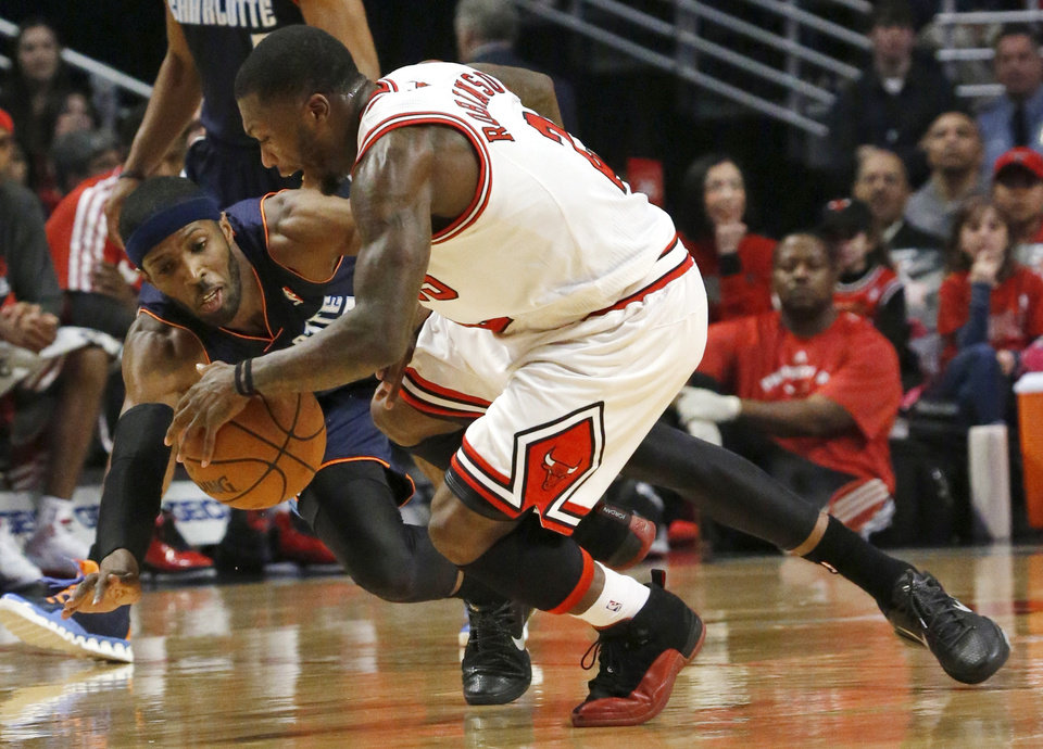 Photo - Chicago Bulls guard Nate Robinson (2) works against Charlotte Bobcats forward Hakim Warrick for a loose ball during the first half of an NBA basketball game Monday, Dec. 31, 2012, in Chicago. (AP Photo/Charles Rex Arbogast)