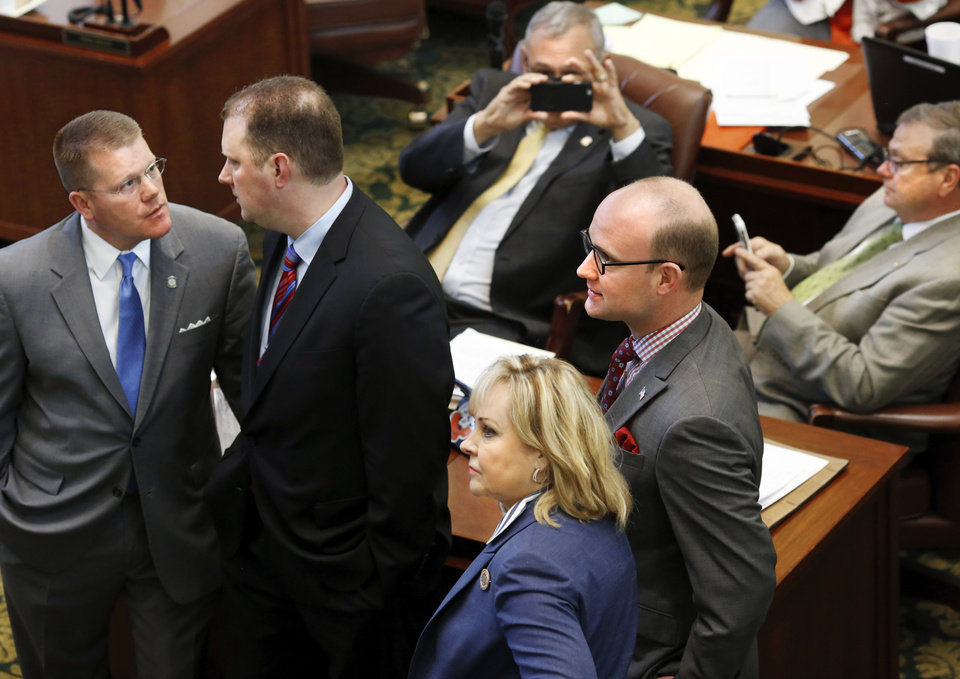 Photo -  Gov. Mary Fallin stands with lawmakers Monday on the House floor to watch as votes are posted on the tally board at the front of the chamber. [Photo by Jim Beckel, The Oklahoman]