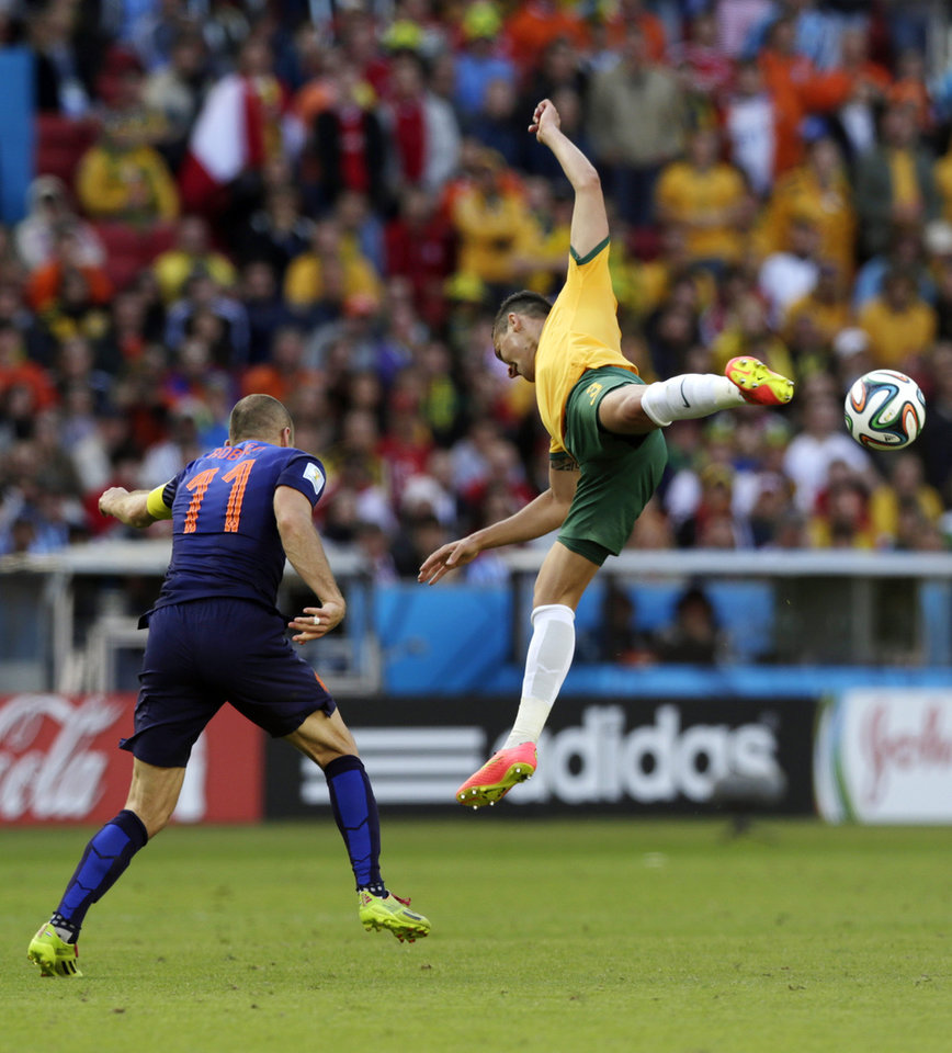 Photo - Australia's Jason Davidson, top, rises above Australia's Tommy Oar during the group B World Cup soccer match between Australia and the Netherlands at the Estadio Beira-Rio in Porto Alegre, Brazil, Wednesday, June 18, 2014. (AP Photo/Wong Maye-E)