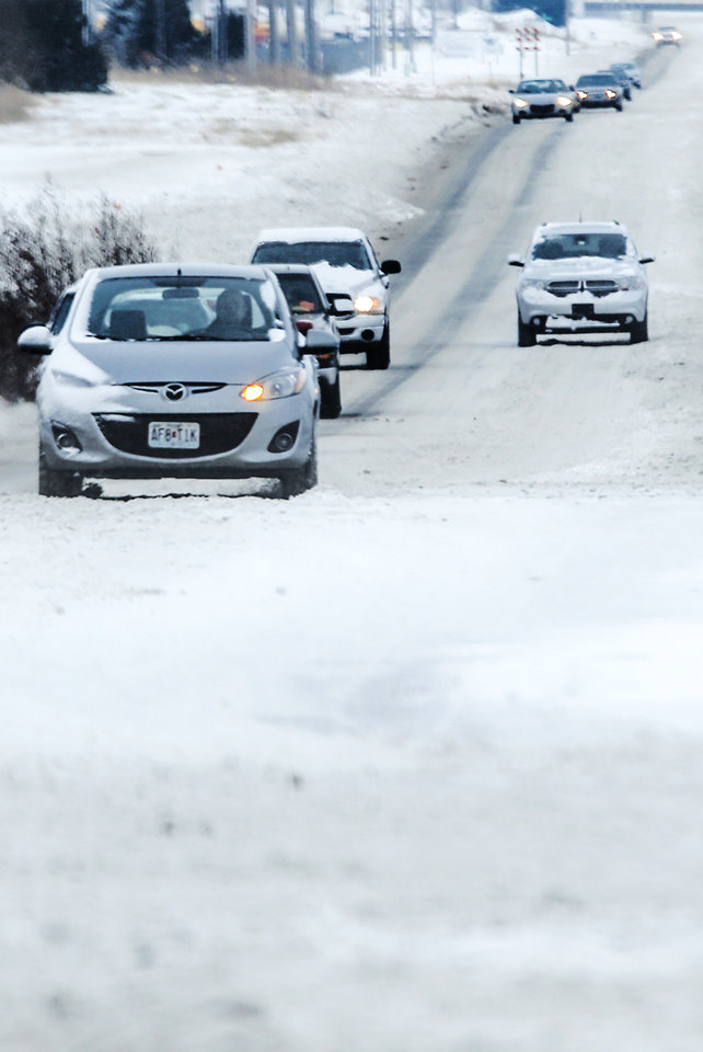 Drivers make their way on snow covered roads during the morning commute in Oklahoma City, Okla. on Friday, Dec. 6, 2013. Photo by Chris Landsberger, The Oklahoman