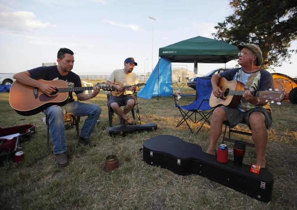 Photo -  Ross Johnson, Jeff Clanton, and Travis Williams play music near their camp during the Woody Guthrie Folk Festival in Okemah, Okla., Thursday, July 12, 2012.  Photo by Garett Fisbeck, The Oklahoman