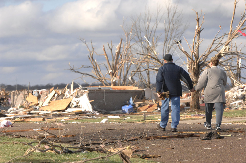 Photo - A couple walks down a street in the Devonshire subdivision on the North side of Washington, Ill., Sunday, Nov. 17, 2013. Intense thunderstorms and tornadoes swept across the Midwest, causing extensive damage in several central Illinois communities while sending people to their basements for shelter. (AP Photo/The Pantagraph, Steve Smedley)