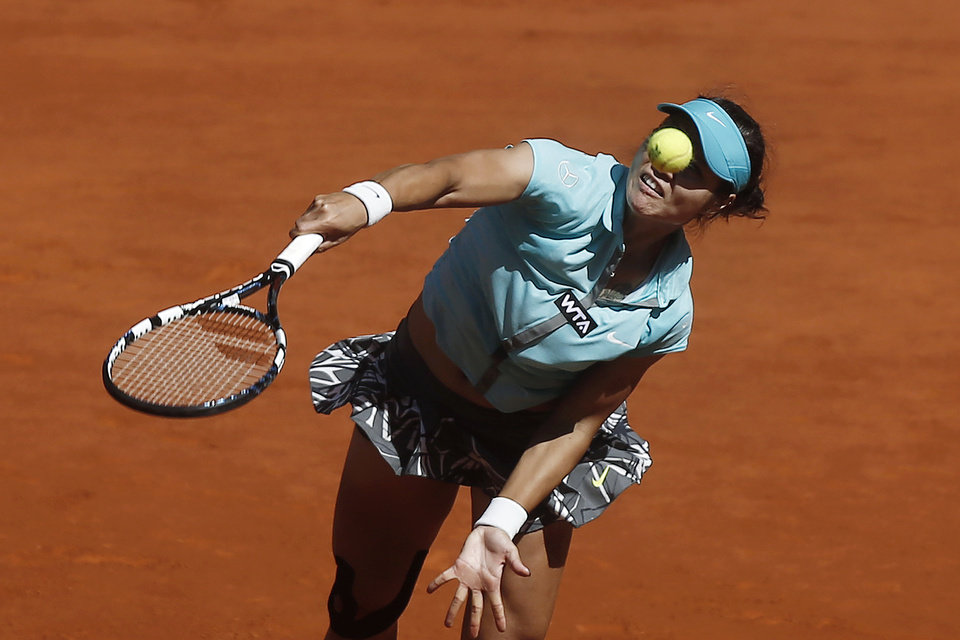 Photo - Na Li from China serves during a Madrid Open tennis tournament match against Kirsten Flipkens from Belgium, in Madrid, Spain, Monday, May 5, 2014. (AP Photo/Andres Kudacki)