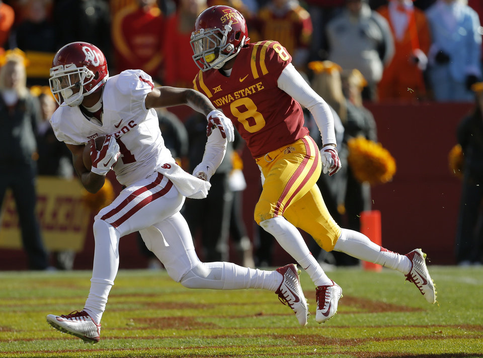 Photo - Oklahoma's K.J. Young (1) scores a touchdown past Iowa State's Kenneth Lynn (8) during a college football game between the University of Oklahoma Sooners (OU) and the Iowa State Cyclones (ISU) at Jack Trice Stadium in Ames, Iowa, Saturday, Nov. 1, 2014. Photo by Bryan Terry, The Oklahoman