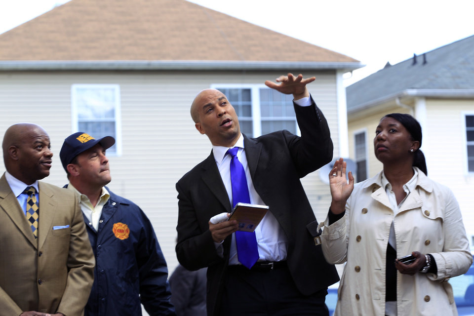 Photo -   Newark Mayor Cory Booker, second right, has a bandaged right hand in front of a home in Newark, N.J., Friday, April 13, 2012, as he describes the scene Thursday when he rescued a woman from her burning home. Booker said Friday he feared for his life as he helped rescue a neighbor from a fire before firefighters arrived. He described how he returned home Thursday night and saw his neighbor's home engulfed in flames. The woman Booker helped save is in stable condition. (AP Photo/Mel Evans)