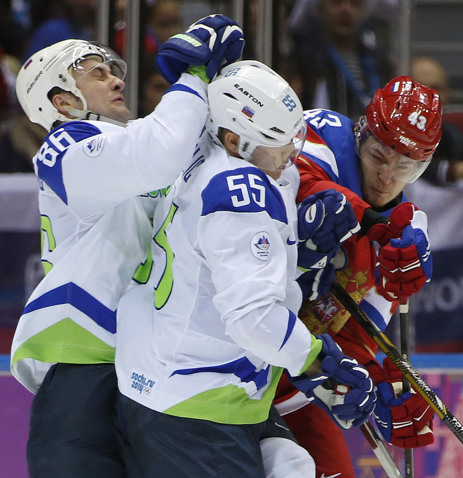 Photo - Slovenia defenseman Sabahudin and forward Robert Sabolic collide with Russia forward Valeri Nichushkin in the second period of a men's ice hockey game at the 2014 Winter Olympics, Thursday, Feb. 13, 2014, in Sochi, Russia. (AP Photo/Julio Cortez)