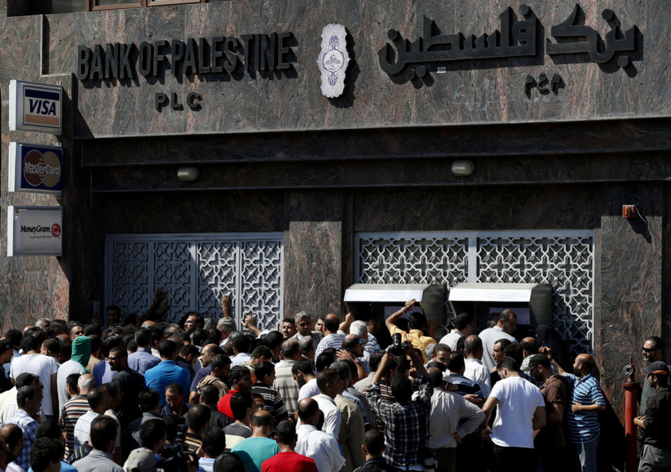 Photo - Palestinians gather to withdraw money from ATM machines in Gaza City, Thursday, July 17, 2014. The Bank of Palestine opened one of its branches in Gaza City's Rimal neighborhood as the cease-fire began, drawing hundreds of people trying to withdraw money. The Israeli military says it has struck 37 targets in Gaza ahead of a five-hour humanitarian cease-fire meant to allow civilians to stock up after 10 days of fighting. Palestinian health officials say that in total, at least 225 Palestinians have been killed. On the Israeli side, one man was killed since July 8.(AP Photo/Lefteris Pitarakis)