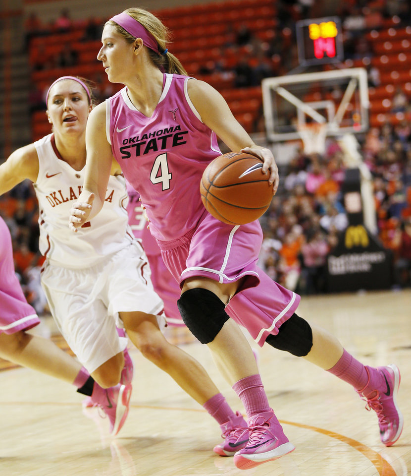 Photo - Oklahoma State's Liz Donohoe (4) drives past Oklahoma's Nicole Kornet (1) in the first half during the women's Bedlam college basketball game between the OU Sooners and the OSU Cowgirls at Gallagher-Iba Arena in Stillwater, Okla., Sunday, Feb. 16, 2014. Photo by Nate Billings, The Oklahoman