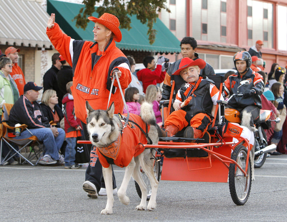 Photo - A child rides in a dog-pulled wagon during the Oklahoma State Cowboy's homecoming parade in downtown Stillwater, OK, Saturday, Oct. 29, 2011. By Paul Hellstern, The Oklahoman