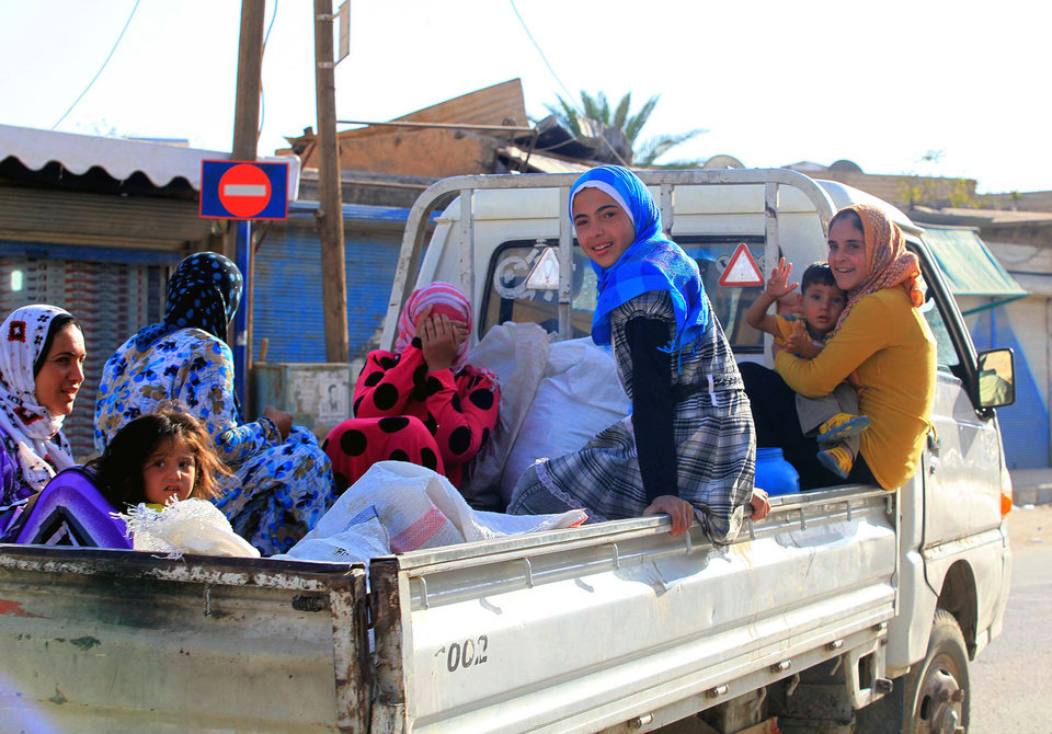 Photo -   Local people travel on the back of a truck in Tel Abyad, Syria, Friday, Oct. 5, 2012. On Friday, a Syrian mortar round hit inside Turkey, causing no injuries, and Turkish troops returned fire, the state-run news agency Anadolu said late Friday, and Turkey deployed more troops near to the border with Syria. (AP Photo)