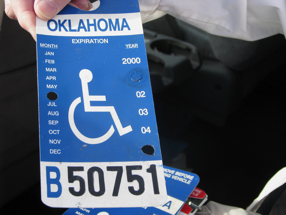 Photo - Handicap Parking Enforcement Specialist Officer David Hoff holds up a tampered placard for inspection. BY VALLERY BROWN, THE OKLAHOMAN