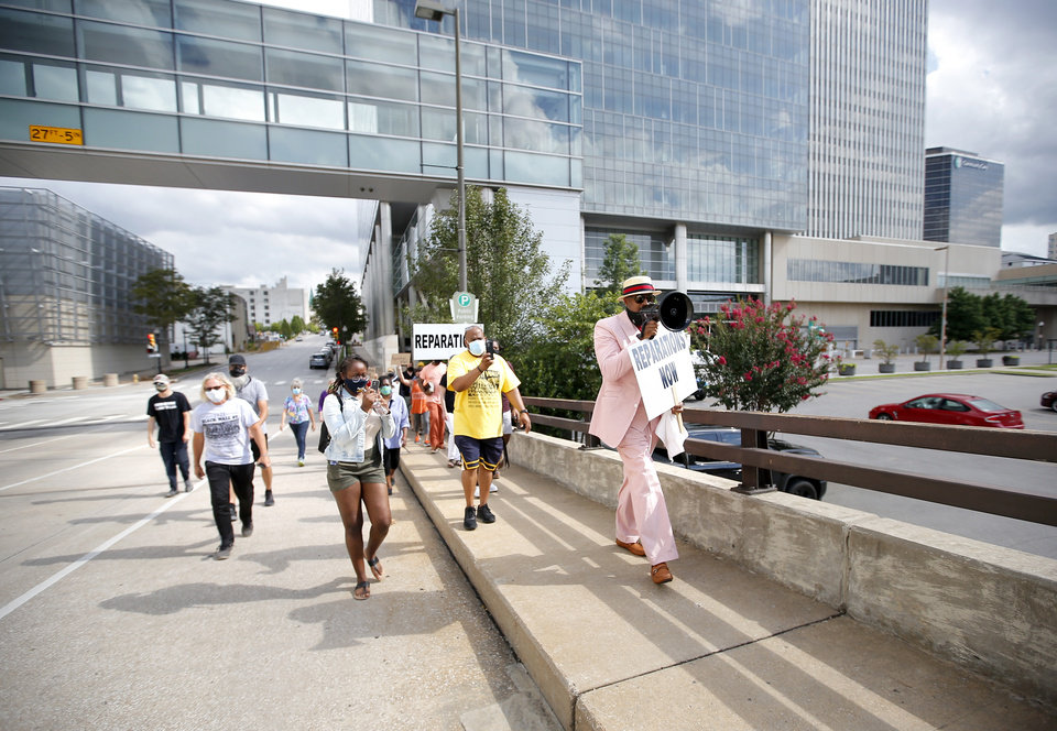 Photo -  The Rev. Robert Turner, senior pastor of Vernon African Methodist Episcopal Church, and supporters march on Wednesday from Tulsa City Hall to his church in Tulsa's Greenwood District. [Sarah Phipps photos/The Oklahoman]