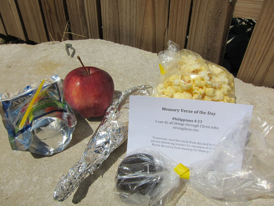 Photo - A recent free lunch delivered to young Oklahoma City apartment residents by Truth Baptist Church included an apple, popcorn, corn dog cookies, juice and a card featuring a Scripture for memorization.  Carla Hinton - The Oklahoman