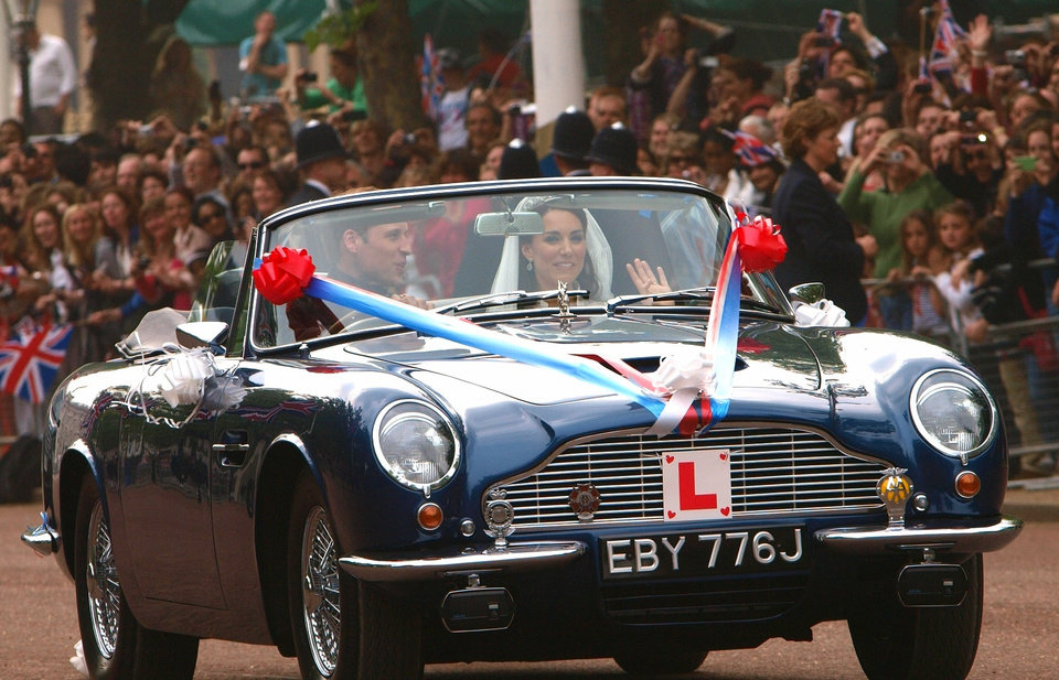 Photo - Britain's Prince William drives his wife, Kate, Duchess of Cambridge on The Mall in London in his father Prince Charles' Aston Martin Volante sports car covered with bunting on their way to Clarence House after their wedding in nearby Westminster Abbey, in London Friday April 29, 2011.(AP Photo/Max Nash, Pool) ORG XMIT: RWAJP138