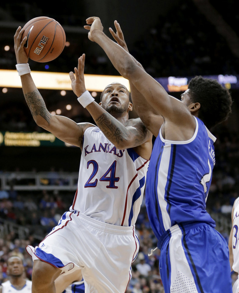 Photo -   Kansas guard Travis Releford (24) gets past Saint Louis forward Dwayne Evans (21) to put up a shot during the first half of an NCAA college basketball game Tuesday, Nov. 20, 2012, in Kansas City, Mo. (AP Photo/Charlie Riedel)