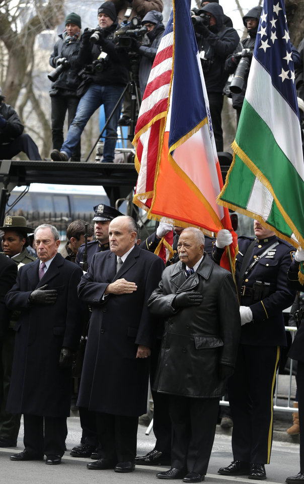 Photo - New York City Mayor Michael Bloomberg, left, and former New York City Mayors Rudolph Giuliani, center, and David Dinkins put their hands over their hearts as a casket containing the body of former New York City Mayor Ed Koch leaves a synagogue after his funeral in New York, Monday, Feb. 4, 2013. Koch was remembered as the quintessential New Yorker during a funeral that frequently elicited laughter, recalling his famous one-liners and amusing antics in the public eye. Koch died Friday of congestive heart failure at age 88. (AP Photo/Seth Wenig)
