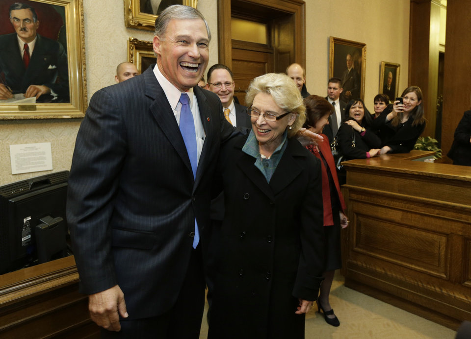 Gov. Jay Inslee, left, is greeted by former Gov. Chris Gregoire, right, in the governor's office after Inslee was sworn in as Governor, Wednesday, Jan. 16, 2013, at the Capitol in Olympia, Wash. Gregoire served two terms as Governor. (AP Photo/Ted S. Warren)