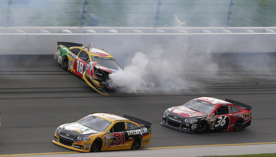 Photo - Drivers Jeff Burton (31) and J J Yeley (36) get past Kyle Busch (18) during a NASCAR Sprint Cup series auto race at Kansas Speedway in Kansas City, Kan., Sunday, Oct. 6, 2013. (AP Photo/Orlin Wagner)