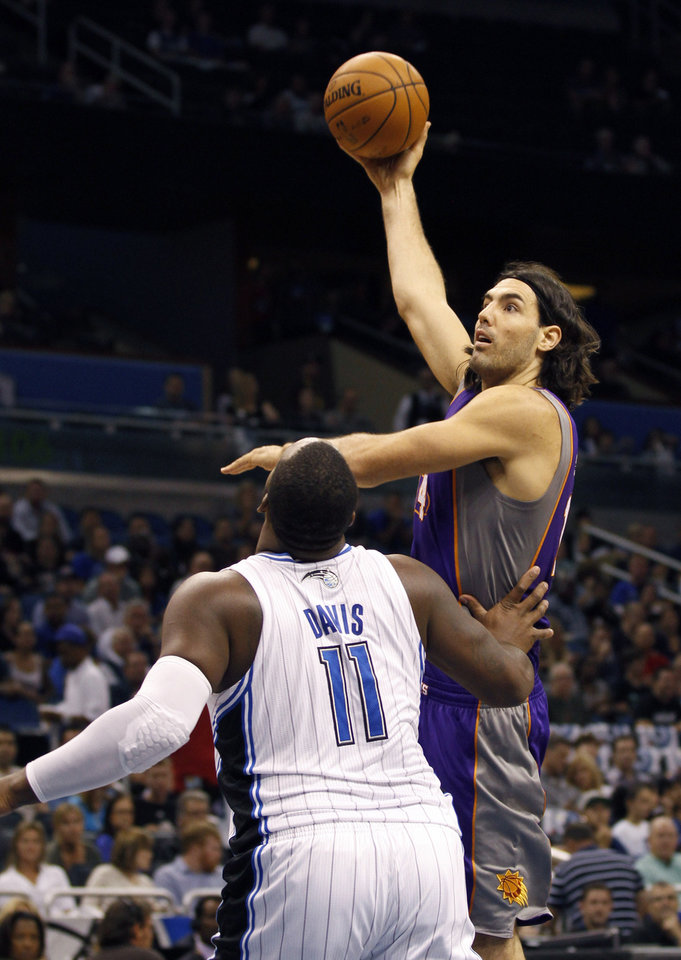 Orlando Magic forward Glen Davis (11) watches the shot of Phoenix Suns forward Luis Scola during the first half of an NBA basketball game in Orlando, Fla., Sunday, Nov. 4, 2012. (AP Photo/Reinhold Matay)